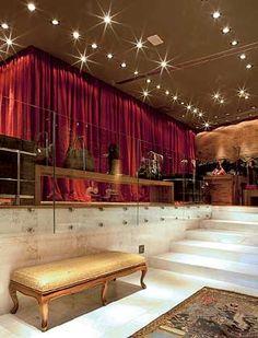A iluminação focada utiliza lâmpadas halógenas; no fechamento dos provadores, cortinas de veludo vermelho