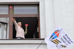 Photo: A pro-Russian activist throws flowers from a window of the regional government headquarters in Luhansk after separatists seized the complex.