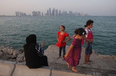 Qatari women still need their husbands' permission to obtain a driving license. Each year, about 100 expat women are jailed for giving birth outside of wedlock. Pictured here are a woman and three children along the Persian Gulf waterfront in Doha.