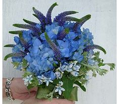 WED-109a This hand-tied bouquet showcases cool shades in blue and purple. Flowers used include blue Hydrangea, purple Veronica, and delicate light blue Tweedia. Stems are tied with a moss green satin ribbon. Price ranges from $175 - $205 depending upon seasonal availability.