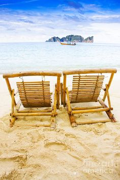 Two Wooden Recliner Chairs Sit On A Thailand Tropical Island Beach Location With Longboat On The Distant Waters, Photograph Taken Phi Phi Island Thailand by Ryan Jorgensen