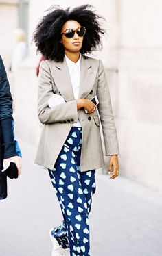 Julia Sarr Jamois wears a button-down shirt, blazer, printed pants, sneakers, and round sunglasses