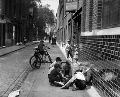 A group of children playing cards and cycling in the streets of Shoreditch in East London c, 1950's.