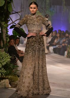 Modle walking the ramp in black and grey embroidered floor length gown for Anamika Khanna at PCJ Delhi Couture week