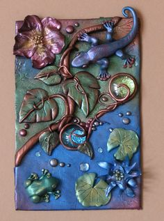 "Tropical Fantasy.  Polymer Clay with glass and crystals. ""I made the 2 flowers, the water lily leaves, 2 big leaves, the frog and the gecko separately and then put them altogether today. I may use it as a book box cover or a journal cover or maybe just a standalone piece to display"" by Robync70."