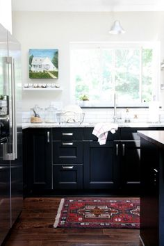 Ikea Ramsjö black kitchen cabinets, white subway tile backsplash and walls, silver hardware, colorful kilim rug