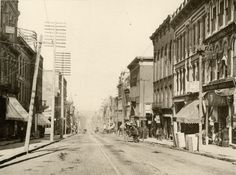 View of North Main St. in Mansfield, Ohio. Streetcar tracks and several horses and wagons are visible. Also, many old businesses and historic buildings.