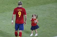 Spain's Fernando Torres (L) and his daughter walk on the pitch after the Spain's team victory against Italy during their Euro 2012 final soccer match at the Olympic Stadium in Kiev July 1, 2012.