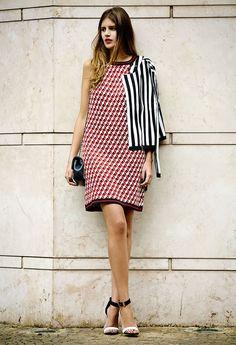 A Sister Mariana Cassou, co-founder e buyer do Gallerist, veste blazer listrado P&B, vestido gráfico vermelho e sandálias preto e branco.