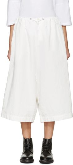 Pillar-leg sarouel-style trousers in white. Drawstring at waistband. Two-pocket styling. Cropped at hem. Zip-fly. Tonal stitching.