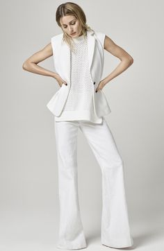 White wide leg trousers, a knit sweater, and lapel vest on Olivia Palermo.