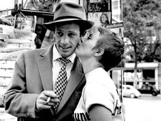 Jean-Paul Belmondo and Jean Seberg kiss in front of a kiosk on the Camps Elysees (A Bout De Souffle), 1959