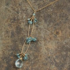 This elegant two-tier goldfill chain necklace features an aquamarine drop and swirl detail. This lovely jewelry is accented with an oval link chain, light apatite and pearl clusters. State: California