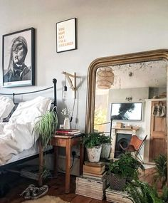 giant mirror behind stacked books and plants