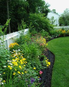 White picket fence over chain link fence with great landscaping