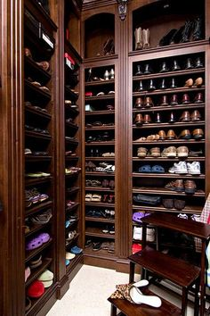 Stunning walk-in closet with custom dark wood shoe storage accented by fluted pilasters.