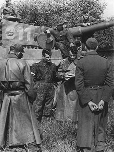 Thumbnail pics 	World War 2 leading tanker ace, SS-Hauptsturmführer (captain) Michael Wittman briefing his tank commanders, Normandy 1944. Decorated with the prestigious Knight's Cross of the Iron Cross with Oak Leaves and Swords, Michael Wittman destroyed 138 allied tanks and 132 anti-tank guns during his career. #photography #war