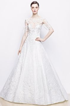 A-line gown in tulle with sweetheart neckline and illusion short sleeves with lace appliqué. Enzoani, 2014
