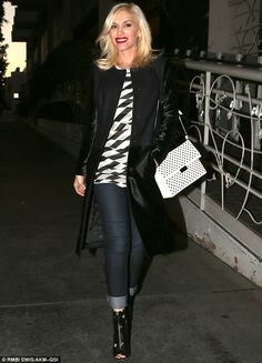 Pregnancy chic: The expecting mother covered her blooming bump in a white and black blouse teamed with skinny jeans, a shiny jacket, and pee...