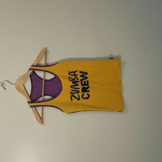 Zumba Instructor Racerback Tank Top Yellow and purple Zumba Fitness trademark racerback tank top. This top has Zumba Crew written on the front and Instructor on the back. It is a size small and fits true to size. It is in excellent used condition. It measures 13 inches width, 14 inches from the bottom to the armpit and 21.5 inches from bottom to rop. Zumba Tops Tank Tops