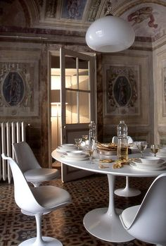 Palazzo Orlandi 1960's style tulip chairs contrast centuries old plaster mural painted walls in dining room