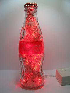 Luminária produzida com garrafa de vidro pequena da marca Coca-Cola, refrigerante comercializado em mais de 200 países.  Além de original, a luminária é duplamente sustentável: a garrafa é um material reciclado e o LED consome menos energia e tem vida útil bem mais longa do que as lâmpadas comuns.  Ideal para cabeceiras, estantes e escrivaninhas. Combina também com ambientes comerciais como lojas, bares e restaurantes.  Características: - São 50 microlâmpadas vermelhas de LED que permitem…