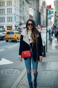 New Year's 2017 in NYC. White sweater with print+ripped jeans+blue velvet boots+blue velvet jacekt+red chain crossbody bag+sunglasses. Winter Casual Outfit 2017