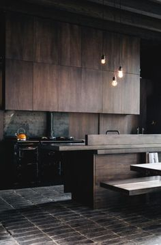 a dark and moody modern kitchen with dark colored wood cabinets and black appliances
