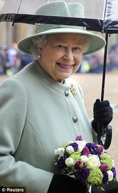 The Queen is undeterred by the wind and rain as she gears up to meet the young scouts.
