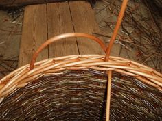 First the handle rod is pushed into the basket firmly on the left side, taken over to the right and pushed through onto the inside of the basket.  A second rod of willow is pushed in close to the hoop on the right hand side.