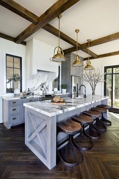 Gorgeous kitchen features gray wash cabinets paired with dark gray and white marble countertops.