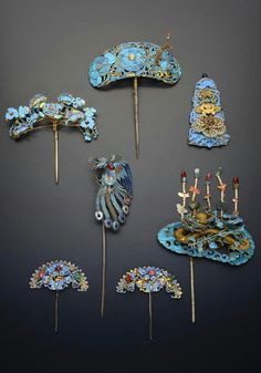 China | Five gilt metal and Kingfisher feather hair ornaments and a plaque; one decorated with a filigree dragon amongst clouds and with five tassels in pearl, jade and other hardstones, another with four geese and a central shou character, the others with designs of butterflies, fruit and flowering foliage, and an enamel hairpin modelled as a peacock | Qing Dynasty | 5'500£ ~ sold (May '15)