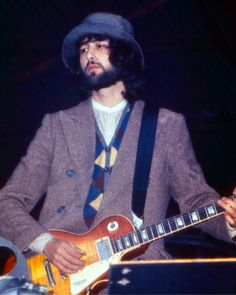 Jimmy Page with a shirt, a sweater vest, a trench coat, and a bucket hat, unusual clothes mix.