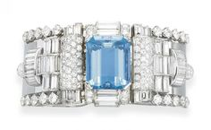 A STYLISH AQUAMARINE AND DIAMOND BRACELET, BY VAN CLEEF & ARPELS   The hinged platinum cuff, centering upon a cut-cornered rectangular-cut aquamarine, with baguette and circular-cut diamond detail, flanked on either side by circular and baguette-cut diamond openwork geometric panels, trimmed by larger circular-cut diamonds, to the polished platinum band, mounted in platinum and 18k white gold, 1955, 2 1/8 ins. diameter, in a Van Cleef & Arpels black leather case  Signed Van Cleef & Arpels
