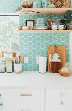 Natural wood accents really pop against white countertops and a blue-green tile backsplash. Link in bio for more kitchen backsplash inspo. Diy Kitchen Remodel, Interior Design Kitchen, Kitchen Remodeling Projects, Diy Kitchen Backsplash, Bohemian Kitchen, Kitchen Style, Kitchen Renovation, Green Kitchen Backsplash, Kitchen Design