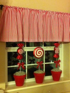 Candy topiaries for the kitchen window sill. Made from clay pots spray painted red. Then I glued a styrofoam ball inside and covered with moss spray painted white. The large candy ornaments are from Hobby Lobby and came attached to the stick which I inserted into the styrofoam. The final touch is a small bow tied onto the stick.