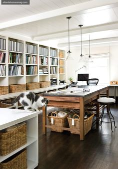 Book- and basket-lined shelves create order in designer Barbara Westbrooks relaxed office space, which mixes modern and traditional through contemporary pendant lighting and an antique French bakers table. 2 of 14Next  Prev