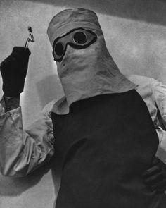 Médico vistiendo ropas protectoras mientras maneja radio para tratamientos (1935)