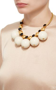 This statement necklace by **Marni** features a sphered decoration in gold, black and ivory.