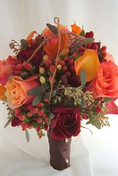 bouquet of calla lily, rose, orange burgundy berries, lots of nice texture and contrast of shapes. Anderson.florist.