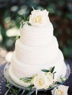 An elegant three-tier white wedding cake with beautiful roses