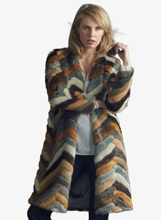 This long length faux fur coat is decorated with a blend of earth tones in an urban chic pattern. - Model wears a size Small. - Midi Length. - Chevron Faux Fur. - Dry Clean Only.