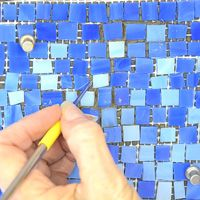 tesserae on mesh being thinset to a vertical surface