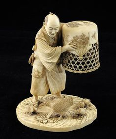 A Japanese ivory group of a man catching chickens, Meiji period, the figure with finely carved clothing and accoutrements, holding a flower engraved basket above a hen and four chicks on a naturalistic oval base, red lacquer seal with engraved two character signature, 5.75in.