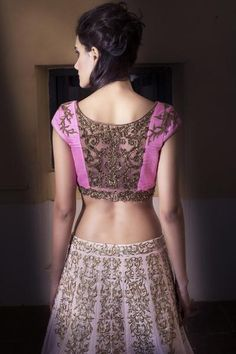 Featuring this rich looking and sophisticated light pink raw silk lehenga with unique motives placement enhanced with gold zari and sparkling crystals. The gold