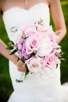 Bride holding light pink, peach, and purple floral bouquet - wedding photo by Michael Norwood Photography