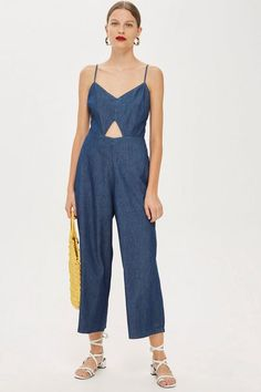 Do denim the modern way with our lightweight jumpsuit in blue with cut out detailing. We're styling it with a pair of on-trend sliders or sandals for a laidback look.