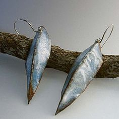 """Turquoise Leaves Enamel Earrings by Evelyn Markasky  - A flat sheet copper was cut then folded and forged to create a soft organic form. Finished with handmade ball end sterling Silver ear wires made especially for these earrings. About 2"""" long. $42.00 On Artful Vision, a portion of your gift item purchased is donated to a participating non-profit of your choice."""