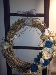 My DIY Spring wreath.  Made with an old Grapevine wreath, spray painted gold.  Hand rolled fabric flowers, with some floral twigs from Michaels.  Mod Podged Welcome banner. Blues/Yellows/Creams/Purples