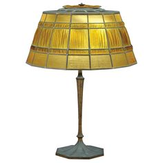 Tiffany Studios Gilt-Bronze and Favrile Glass Linenfold Lamp  First quarter of the 20th century  The paneled shade in frosted amber colored glass, stamped TIFFANY STUDIOS NEW YORK 1952, on a tapering paneled columnar standard ending in a domed octagonal foot, conforming cap, the base stamped TIFFANY STUDIOS NEW YORK 560.